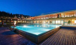 Beleuchtetes Badehaus am Abend im Hotel Das Kranzbach