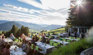 Menschen frühstücken auf der Sonnenterrasse mit Blick auf die Alpen