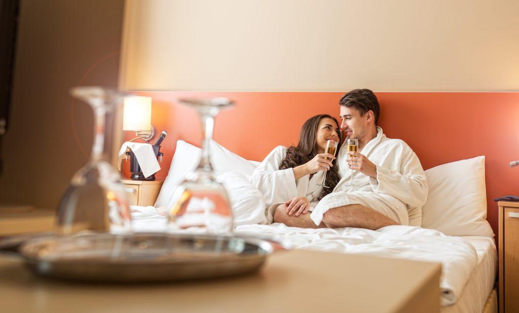 Paar entspannt mit Sekt auf Bett