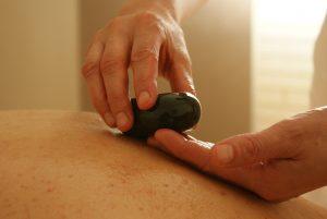 Masseur legt die heißen Steine auf den Rücken einer Patientin